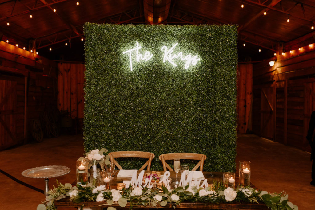 Wood Farm Sweetheart Table with Eucalyptus Greenery Garland and Cross Back Chairs in front of Boxwood Hedge Wall with Neon Sign