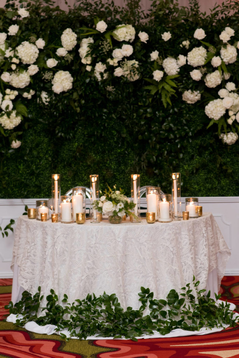 Elegant Wedding Reception Decor, Sweetheart Table with Ivory Lace Linen, Greenery Leaves, Gold and White Candles, Greenery Backdrop with White Hydrangeas and Roses | Tampa Bay Wedding Planner Parties A'la Carte | St. Pete Wedding Venue The Vinoy | Wedding Rentals A Chair Affair | Wedding Florist Bruce Wayne Florals