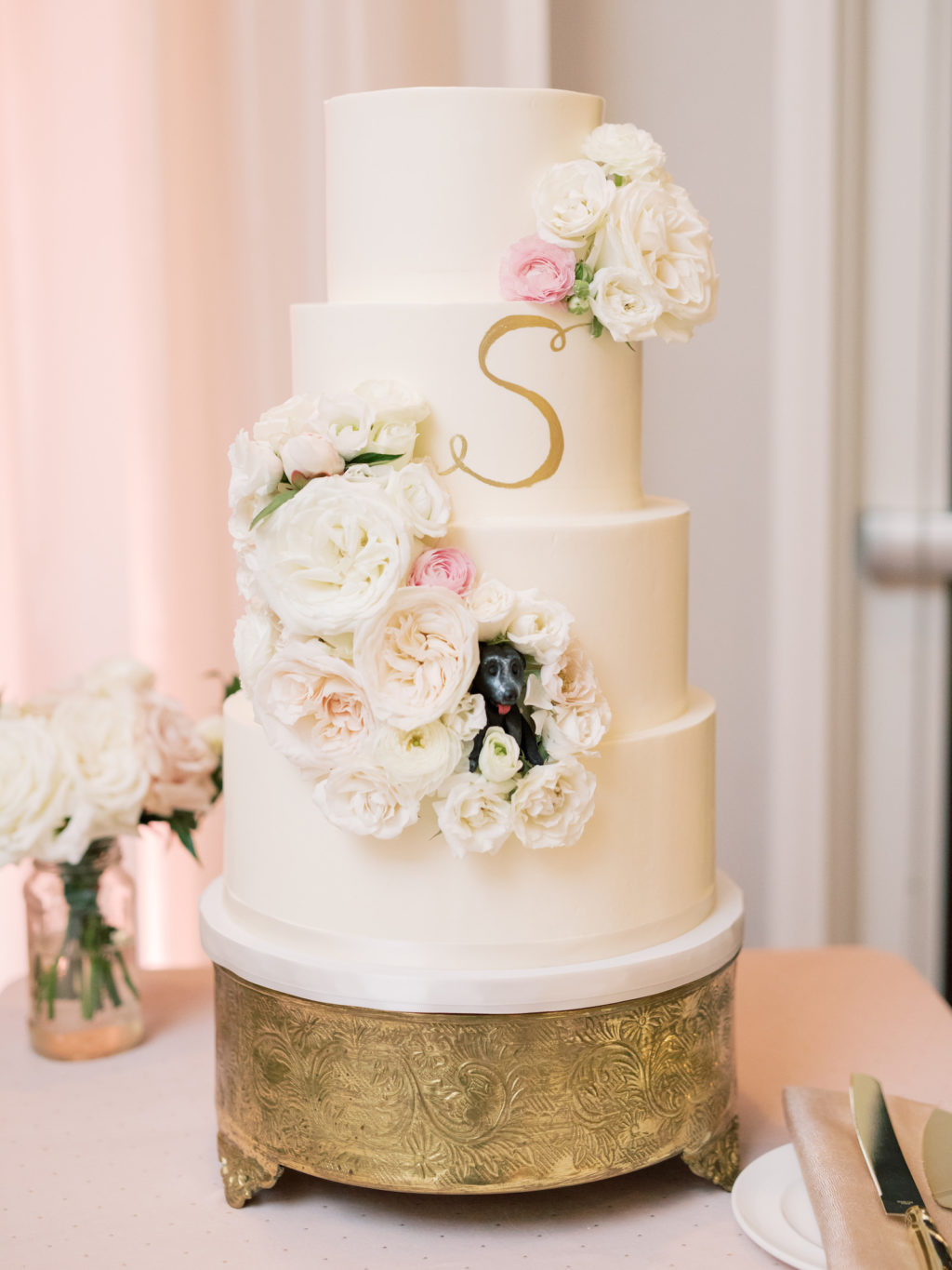 Classic Four Tier White Wedding Cake with Gold Painted Initial and Cascading Blush Pink and Ivory Roses with Unique Dog Figurine Popping Out of Middle Tier Wedding Cake | Tampa Bay Wedding Baker The Artistic Whisk