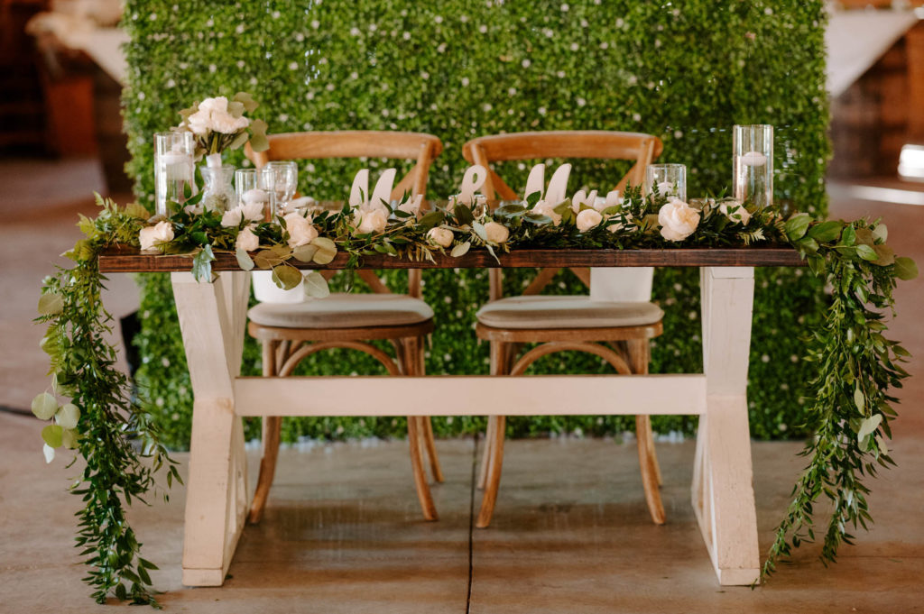 Wood Farm Sweetheart Table with Eucalyptus Greenery Garland and Cross Back Chairs in front of Boxwood Hedge Wall