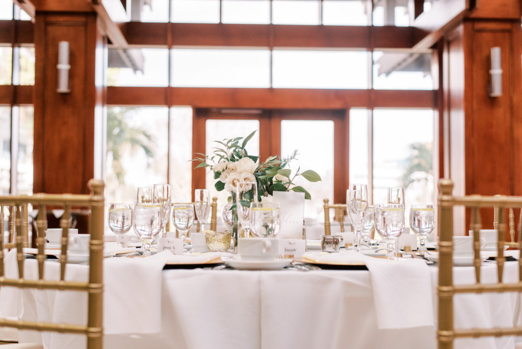 Modern Minimal Wedding Reception Decor, White Table with Gold Chiavari Chairs, Low Greenery and White Roses Floral Centerpiece | Tampa Bay Wedding Photographer Kera Photography | St. Pete Wedding Venue Poynter Institute | Amici's Catered Cuisine