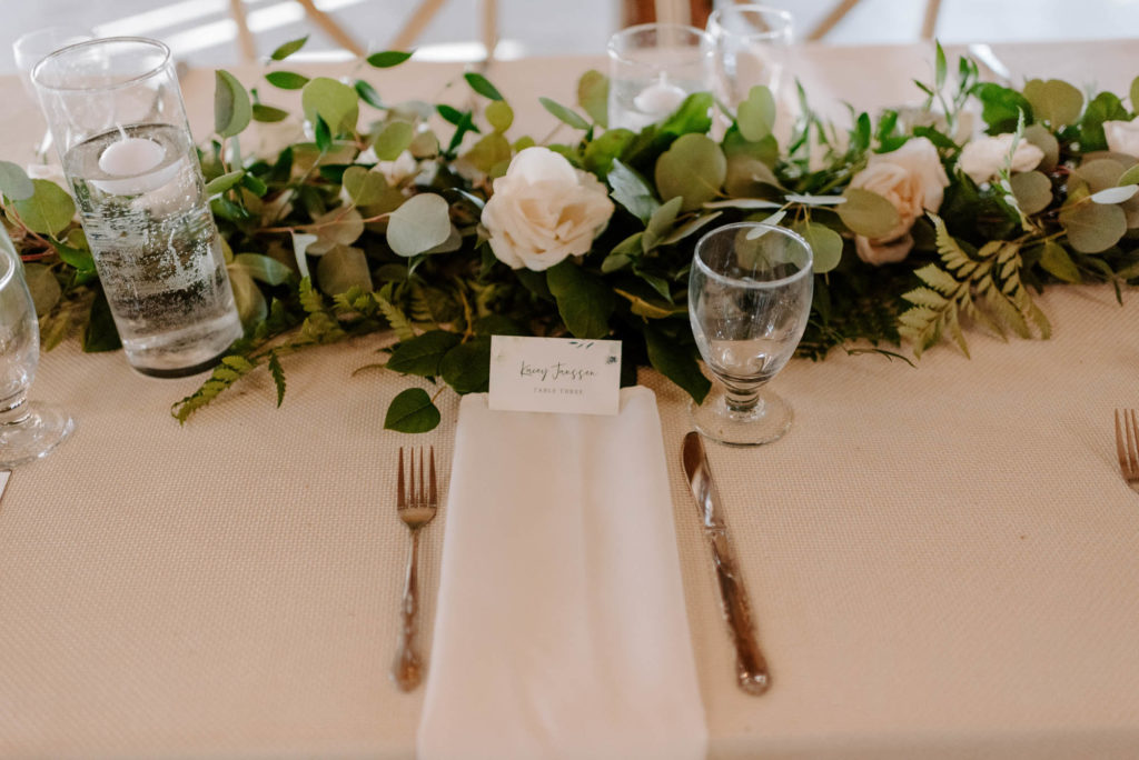 Long Feasting Tables with White Linens and Rose and Eucalyptus Greenery Garland Centerpieces with Floating Candles and White Napkins