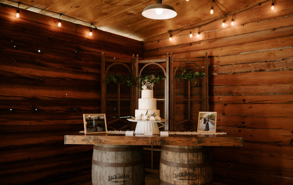 Rustic Plant City Wedding Wood Barrel Cake Table with Framed Engagement Photos | Three Tier Buttercream Wedding Cake with Fresh Flowers and Gold Calligraphy Cake Topper