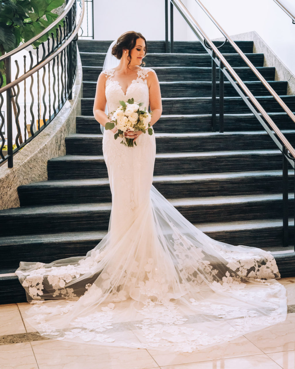 Indoor Bridal Portrait on Staircase | Lace Sheath V Neck Illusion Sleeve Bridal Gown Wedding Dress with Sheer Embroidered Train | Simple White Rose Wedding Bouquet with Eucalyptus Greenery | Femme Akoi Beauty Studio | Bonnie Newman Creative