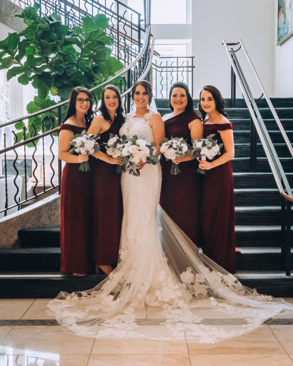 Indoor Bridal Party Portrait on Staircase | Lace Sheath V Neck Illusion Sleeve Bridal Gown Wedding Dress with Sheer Embroidered Train | Simple White Rose Wedding Bouquets with Eucalyptus Greenery | Burgundy Maroon Long Bridesmaid Dresses by David's Bridal | Femme Akoi Beauty Studio | Bonnie Newman Creative