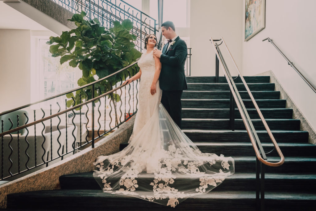 Indoor Bride and Groom Portrait on Staircase | Lace Sheath V Neck Illusion Sleeve Bridal Gown Wedding Dress with Sheer Embroidered Train | Groom Wearing Classic Black Suit Tux