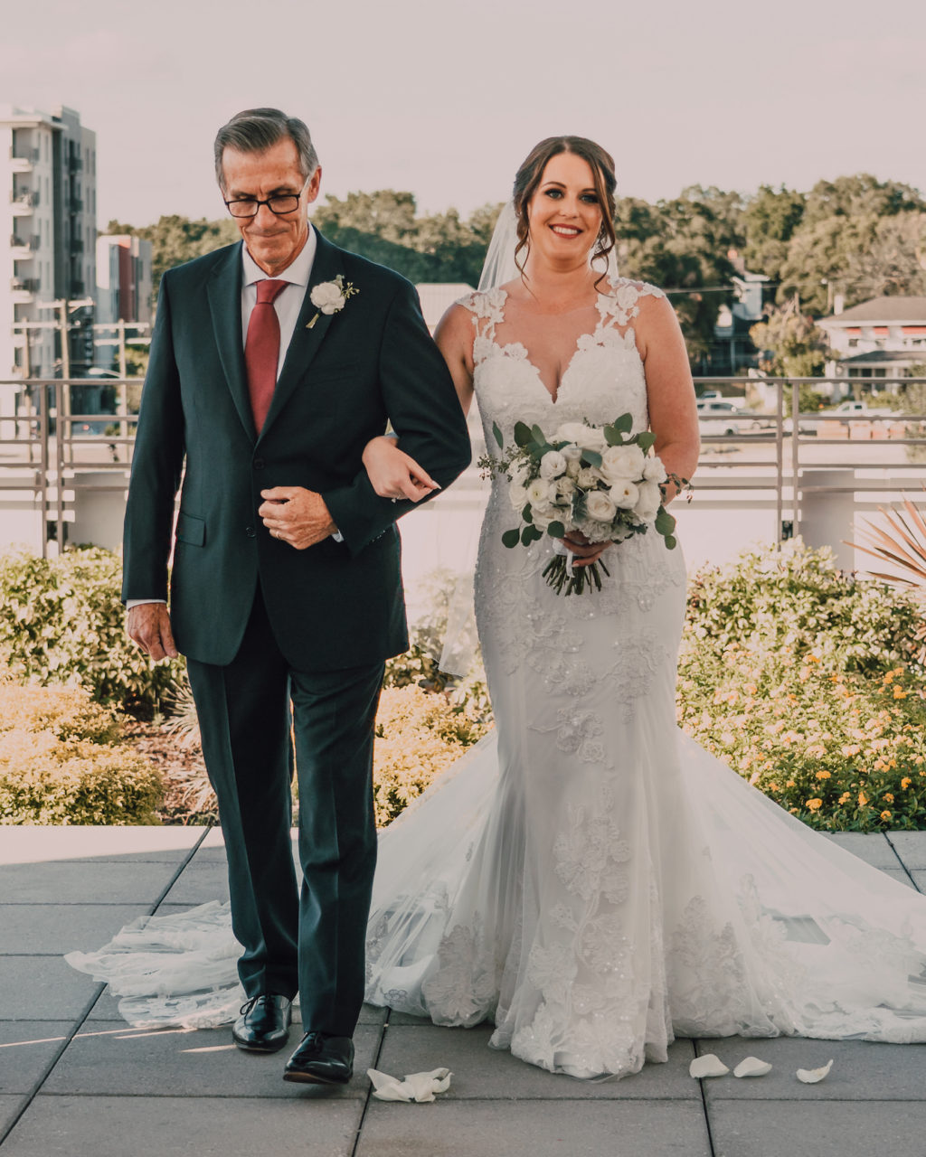 Bride Walking Down the Aisle with Dad at Rooftop Wedding Ceremony | Lace Sheath V Neck Illusion Sleeve Bridal Gown Wedding Dress with Sheer Embroidered Train | Simple White Rose Wedding Bouquet with Eucalyptus Greenery