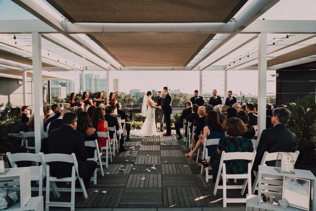 Bride and Groom Exchanging Vows During Tampa Heights Rooftop Wedding Ceremony at Rooftop 220 with white Garden Chairs