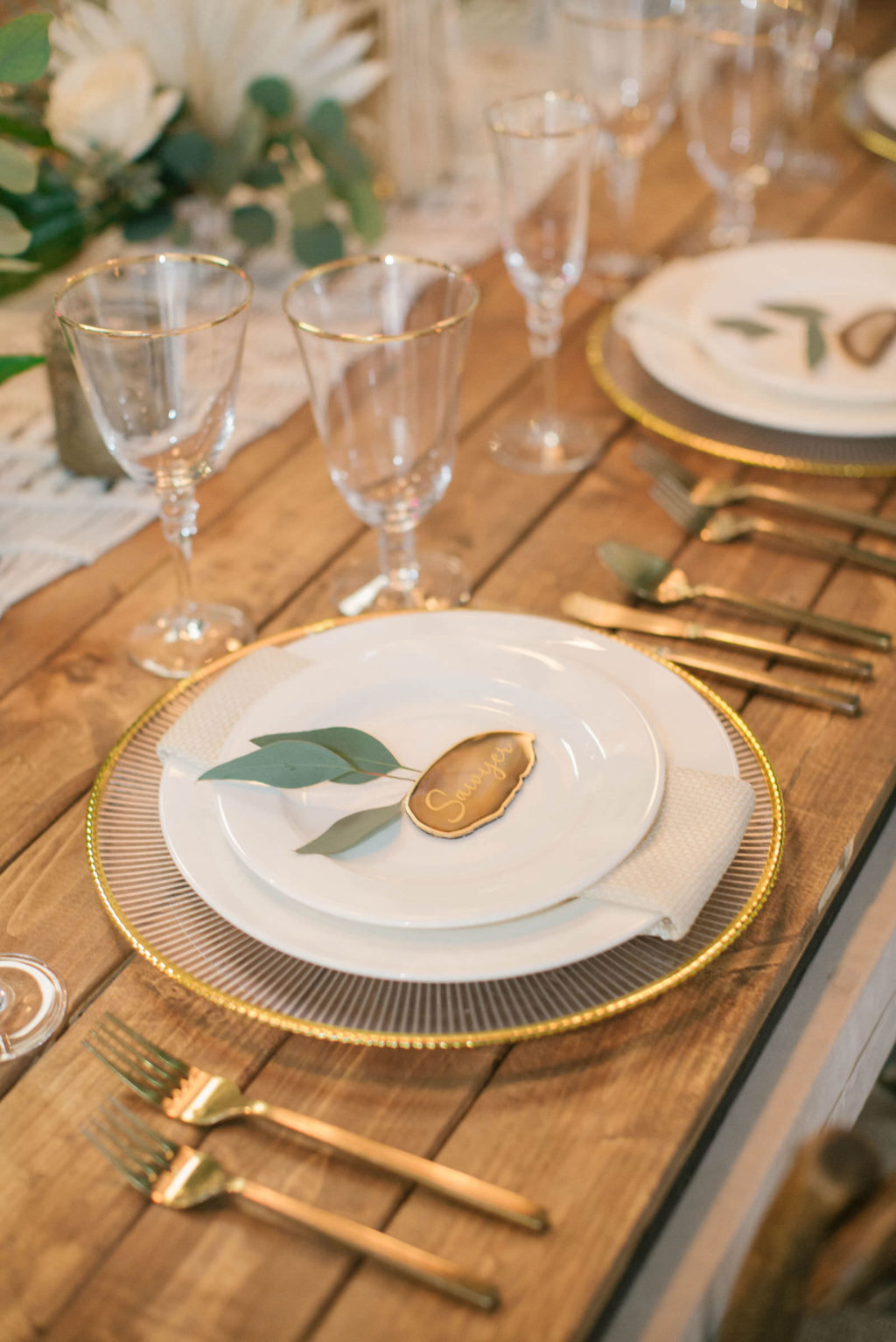 Boho Modern Gold and White Charger with Eucalyptus Greenery Name Card and Golf Flatware on Wooden Feasting Table | Reception Table Decor Ideas | Styled With Love at St. Pete Beach Wedding Venue Bellwether Beach Resort