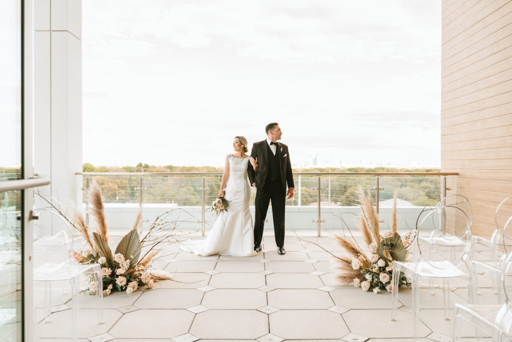 Organic Boho Modern White and Brown Rooftop Wedding Ceremony Flowers with Peach Roses, Gold Leaves, Feathers, and Ghost Chairs | Tampa Bay Wedding Florist Monarch Events | Planner and Designer UNIQUE Weddings + Events | Venue Aloft/Element Midtown | Photographer and Videographer Bonnie Newman Creative | Rentals A Chair Affair