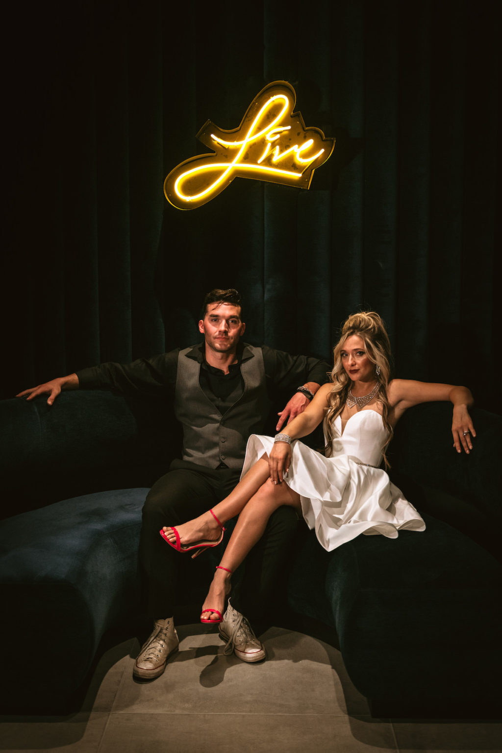 Urban and Edgy Bride in Strapless Short Wedding Dress with Red High Heels, Groom in Black Dress Shirt and Pants with Gray Vest on Couch and Yellow Neon Sign in Backdrop | Tampa Bay Wedding Photographer Bonnie Newman Creative | Wedding Venue Aloft/ Element Midtown Tampa | Wedding Designer and Planner UNIQUE Weddings + Events | Wedding Lighting Spark Wedding Events | Wedding Rentals A Chair Affair | Wedding Dress Truly Forever Bridal | Wedding Hair and Makeup Adore Bridal Services | Wedding Jewelry Accessories International Diamond Center