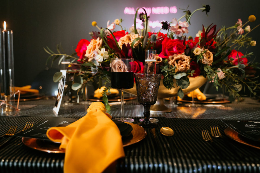 Urban and Edgy Wedding Reception Decor, Black Wall, Water Goblets, Table Linens, Gold Charger, Yellow Mustard Linen Napkin, Red and Yellow Roses with Greenery Floral Centerpiece | Tampa Bay Wedding Photographer Bonnie Newman Creative | Wedding Designer and Planner UNIQUE Weddings + Events | Wedding Venue Aloft/ Element Midtown Tampa | Wedding Floral and Decor Monarch Events and Design | Wedding Lighting Spark Wedding Events | Wedding Rentals A Chair Affair | Wedding Linens Over the Top Rental Linens