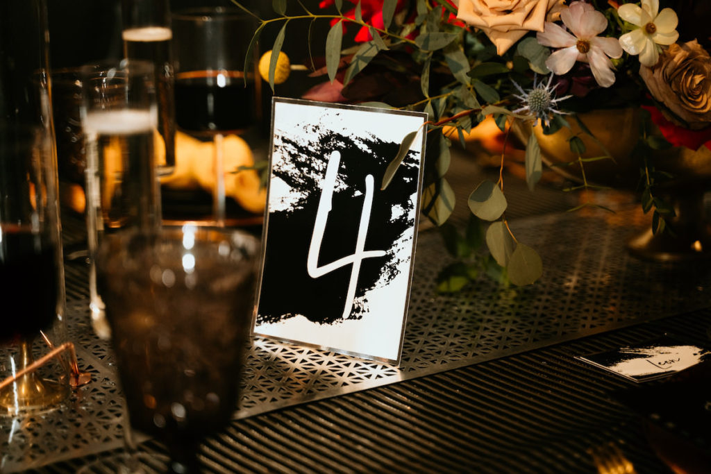 Urban and Edgy Wedding Reception Decor, Unique White with Black Ink Splatter Table Number, Black Wall, Water Goblets, Unique Textured Table Linens and Silver Textured Table Runner, Black Candlesticks, Gold Chargers, Yellow Mustard Linen Napkin, Red and Yellow Roses with Greenery Floral Centerpiece | Tampa Bay Wedding Photographer Bonnie Newman Creative | Wedding Designer and Planner UNIQUE Weddings + Events | Wedding Venue Aloft/ Element Midtown Tampa | Wedding Floral and Decor Monarch Events and Design | Wedding Lighting Spark Wedding Events | Wedding Rentals A Chair Affair | Wedding Linens Over the Top Rental Linens