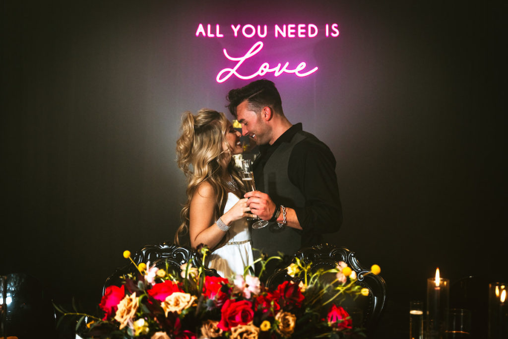 """Edgy and Urban Wedding Reception Decor, Black Wall with Pink Neon Sign """"All You Need is Love"""", Red and Yellow Rose Floral Centerpiece, Bride and Groom with Glass of Champagne 