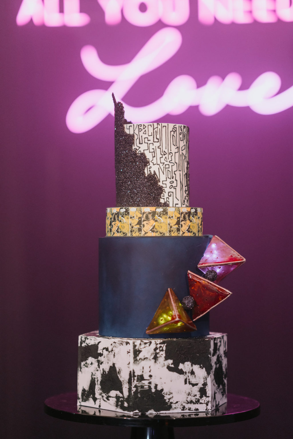 Unique Edgy and Urban Black, White, and Gold Round and Geometric Wedding Cake with Art Deco Inspo Design, Red 3D Geometric Triangles | Tampa Wedding Photographer Bonnie Newman Creative | Wedding Cake The Artistic Whisk | Wedding Designer and Planner UNIQUE Weddings + Events | Wedding Lighting Spark Weddings and Events