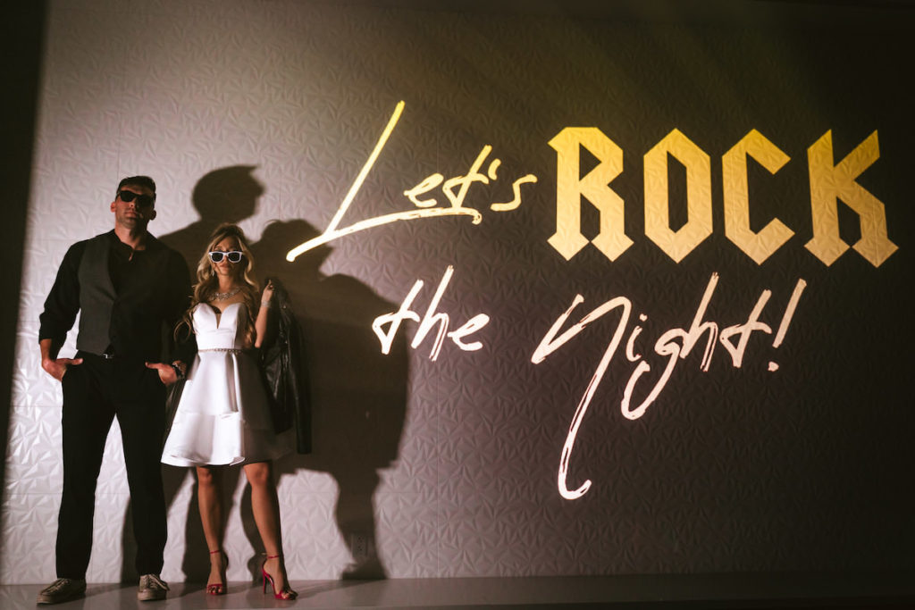 Urban and Edgy Bride in Strapless Short Wedding Dress with Red Heels, Leather Jacket, Sunglasses, Groom in Black Dress Shirt and Pants with Gray Vest and Sunglasses, Black Wall Backdrop and Gold Let's Rock the Night Backdrop | Tampa Bay Wedding Photographer Bonnie Newman Creative | Wedding Designer and Planner UNIQUE Weddings + Events | Wedding Dress Truly Forever Bridal | Wedding Hair and Makeup Adore Bridal Services