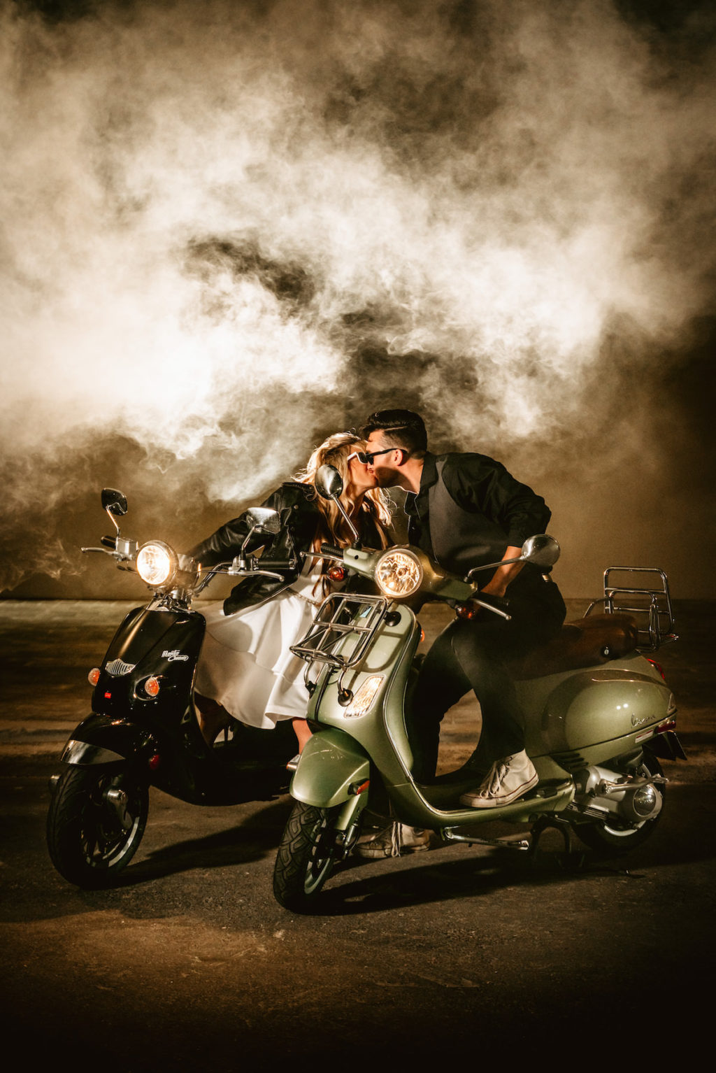 Urban and Edgy Bride in Leather Jacket on Silver Moto Scooter, Groom in Black Dress Shirt and Pants with Gray Vest on Black Scooter and Smoke | Tampa Bay Wedding Photographer Bonnie Newman Creative | Wedding Designer and Planner UNIQUE Weddings + Events