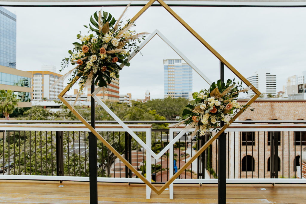 Boho St. Pete Florida Wedding at Red Mesa Events Rooftop | Geometric Diamond Ceremony Arch Floral Spray Arrangement with White and Copper Quicksand Roses, White Stock, Pampas Grass, and Tropical eucalyptus Greenery
