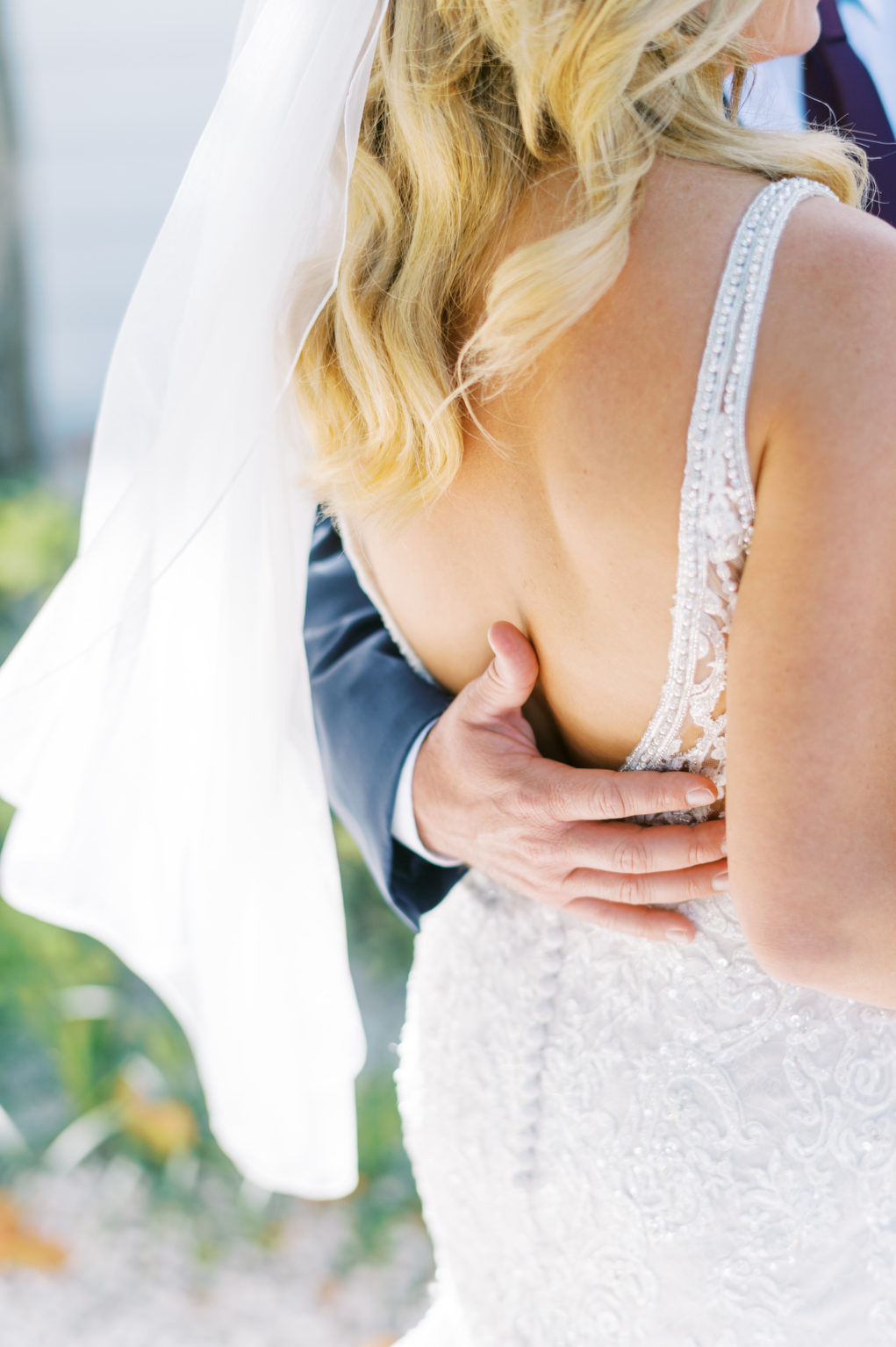 Tampa Groom Hand on Back of Bride Portrait Wearing Open Back Lace and Beaded Wedding Dress