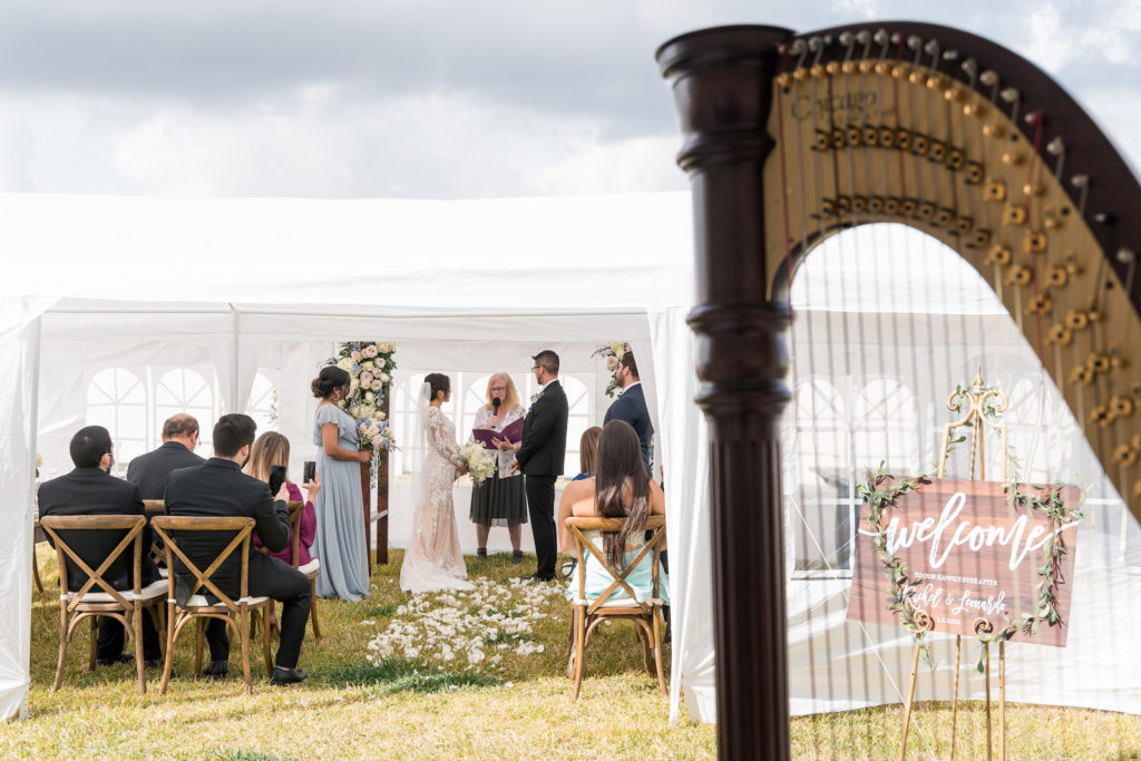Bride and Groom Exchanging Wedding Vows Under White Tent During Rustic Wedding Ceremony | Tampa Bay Wedding Planner Eventfull Weddings