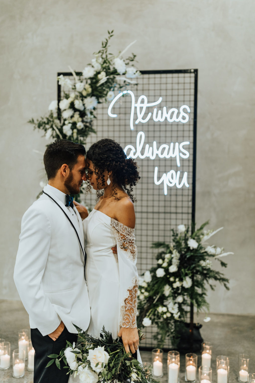 Black Modern Industrial Metal Screen Wedding Ceremony Backdrop Panel with Neon Sign, Candles, and Asymmetrical Floral Arrangements of White Roses and Winter Pine Greenery | Indoor Bride and Groom Portrait | Groom Wearing Classic Formal White Jacket with Black Lapel and Bow Tie | Off the Shoulder Lace Sleeve Sheath Wedding Gown Bridal Dress | Amber McWhorter Photography