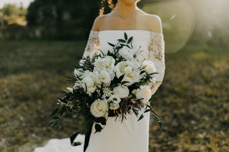 Florida Winter Wedding Bouquet with White Peony Garden Roses, Ranunculus, and Pine Greenery | Off the Shoulder Lace Sleeve Wedding Gown Bridal Dress | Amber McWhorter Photography