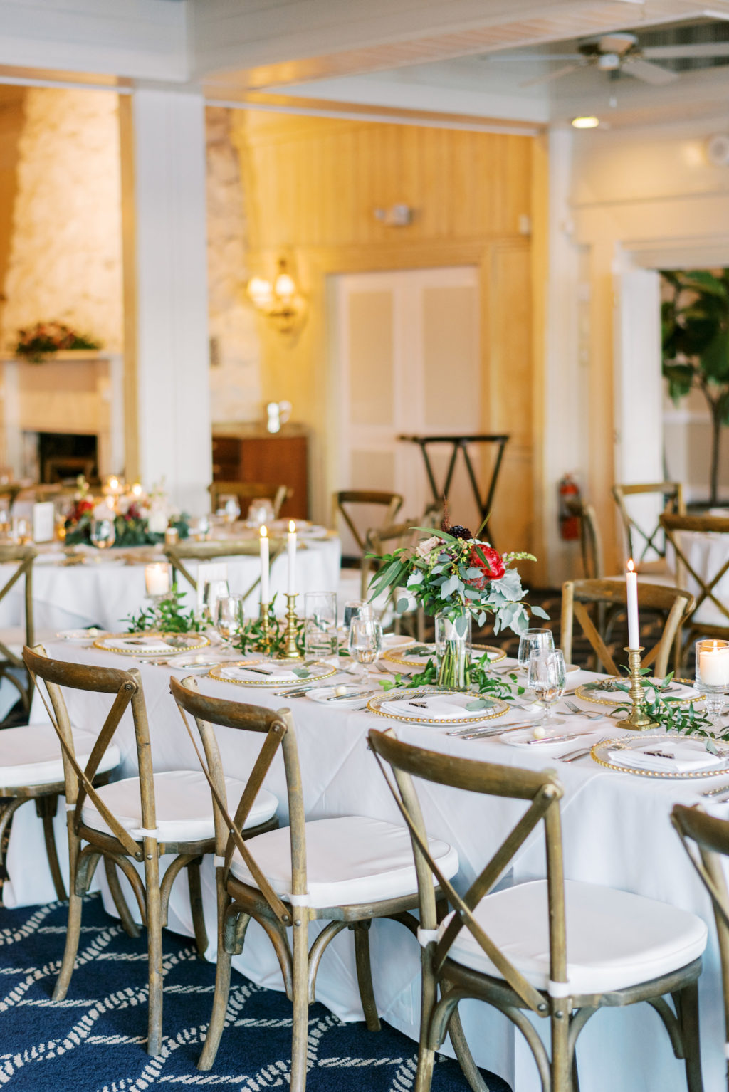 Rustic Romantic Wedding Reception Decor, Long Feasting Table with White Linen, Wooden Cross Back Chairs, Low Greenery and Red Floral Centerpiece, Gold Candlesticks   Tampa Bay Wedding Rentals A Chair Affair   Clearwater Wedding Venue Carlouel Beach and Yacht Club