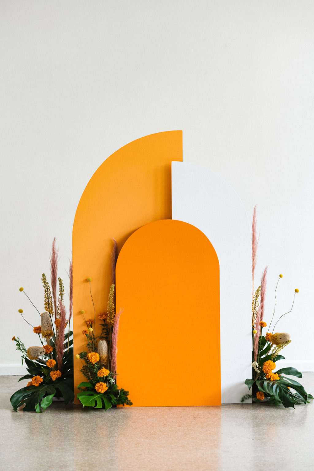 Vibrant Eclectic Mid Century Modern Geometric Orange and White Wedding Ceremony Arch Decor, Monstera Palm Leaves, Orange Flowers and Pampas Grass