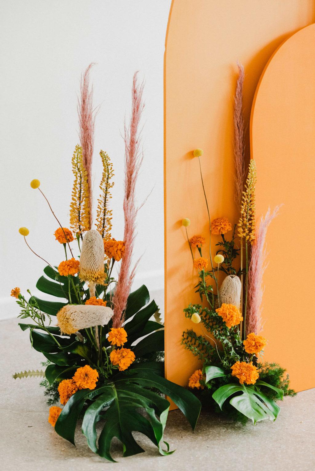 Vibrant Wedding Ceremony Decor, Monstera Palm Leaves, Orange Marigolds, Pampas Grass, and Yellow Flower Arrangements