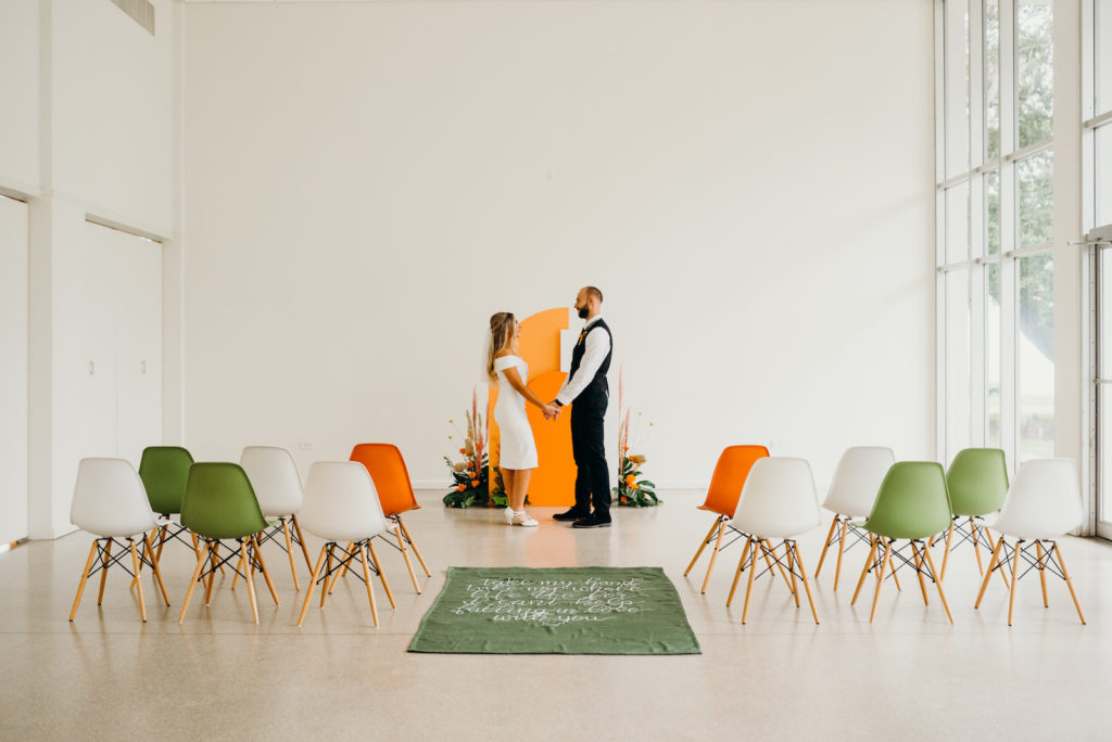 Tampa Retro Eclectic Mid Century Modern Wedding Ceremony Decor, Bride and Groom Exchanging Wedding Vows, Orange and White Geometric Arch, Monstera Leaves, Orange Marigolds, Pampas Grass Flower Arrangements, Green, White and Orange Eames Chairs, Green Carpet Aisle Runner with White Script Quote | Wedding Venue Tampa Garden Club
