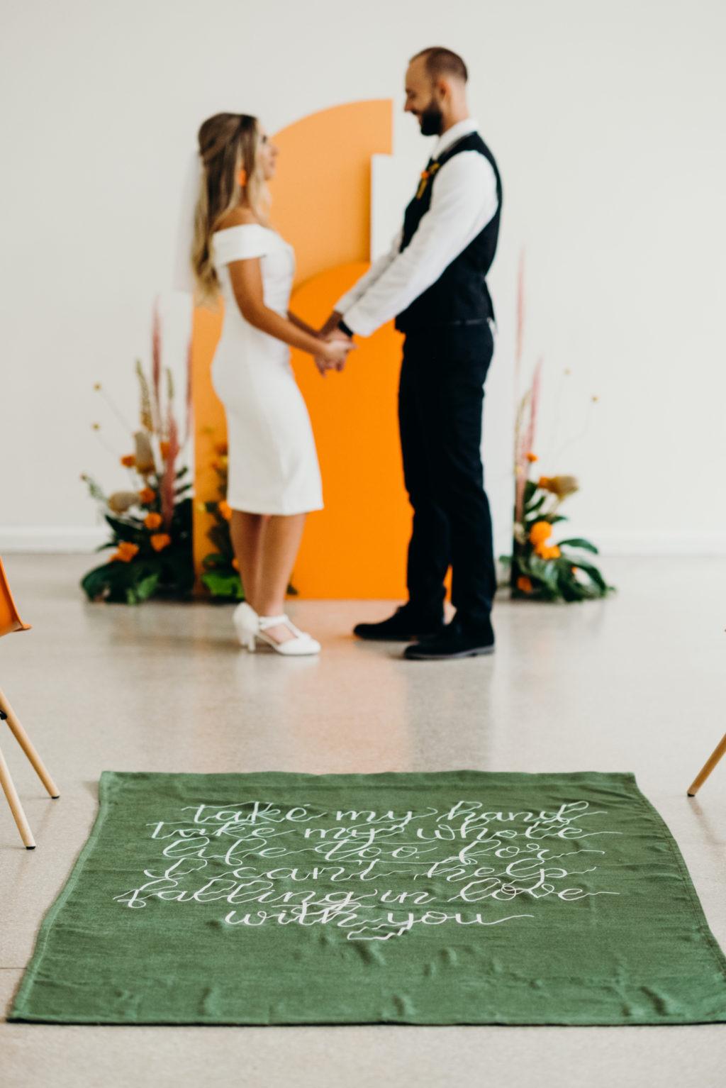 Retro Mid Century Wedding Ceremony Decor, Green Carpet Aisle Runner White Script Quote, Bride and Groom Exchanging Wedding Vows | Wedding Venue Tampa Garden Club