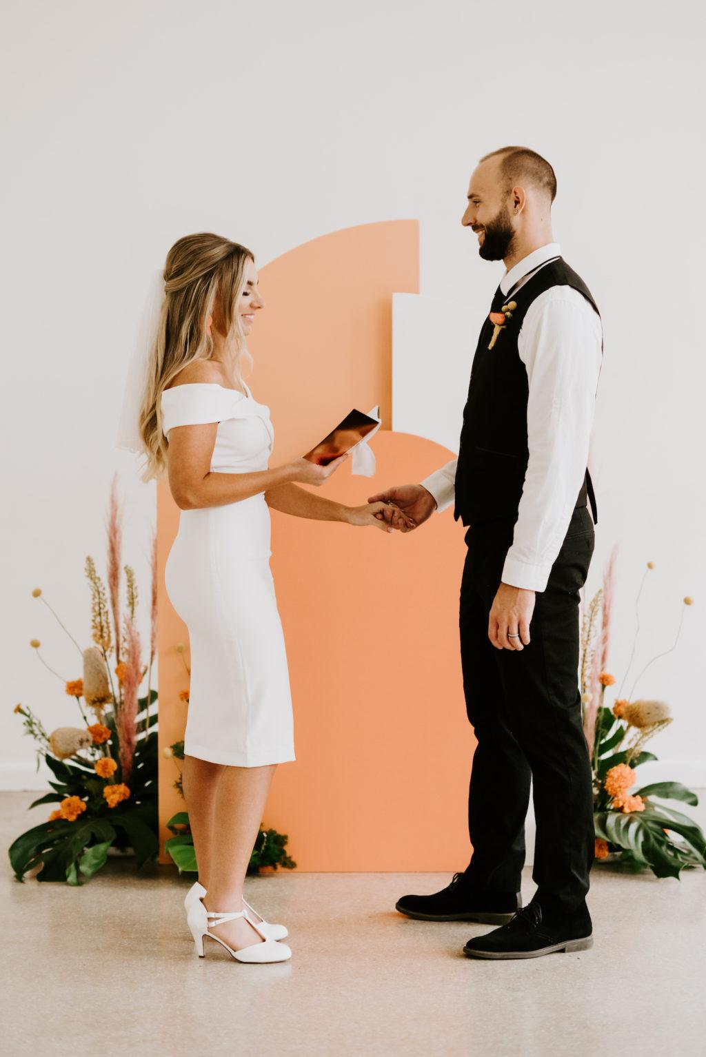 Retro Mid Century Modern Wedding Ceremony Bride and Groom Exchanging Wedding Vows, Orange and White Geometric Arch, Monstera Palm Leaves, Orange Marigolds, Pampas Grass Flower Arrangements