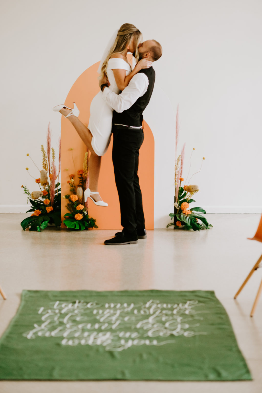Retro Mid Century Modern Wedding Ceremony Bride and Groom Exchanging Kiss After Wedding Vows, Orange and White Geometric Arch, Monstera Palm Leaves, Orange Marigolds, Pampas Grass Flower Arrangements, Green Carpet with Script White Quote Aisle Runner Wedding Venue Tampa Garden Club