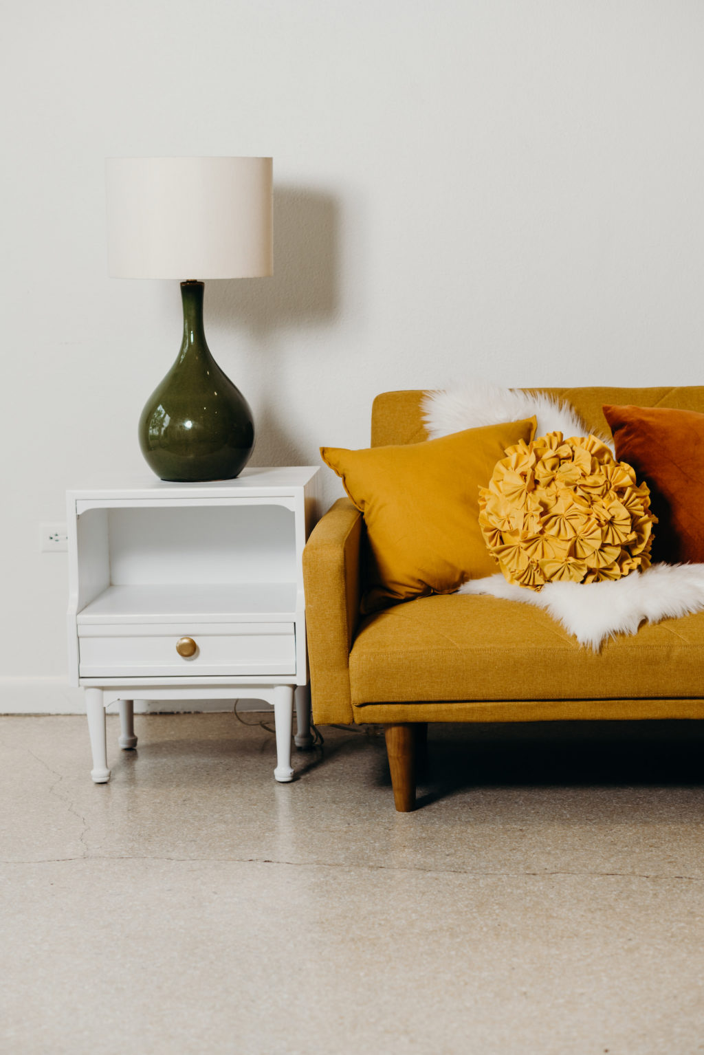 Retro Mid Century Modern Furniture, Mustard Yellow Couch with Pillows, White Fur Blanket, White Side Table with Green Lamp | Wedding Venue Tampa Garden Club