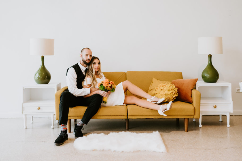 Retro Bride in Off the Shoulder Mid-Length Wedding Dress Holding Colorful Orange Floral Bouquet and Groom on Mustard Yellow Couch with Orange Pillows, White Fur Rug, White Side Tables with Green Lamps