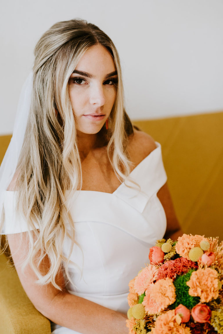 Mid Century Modern Bride with Hair Half Up Wearing Off the Shoulder Wedding Dress Holding Retro Orange and Yellow Floral Bouquet