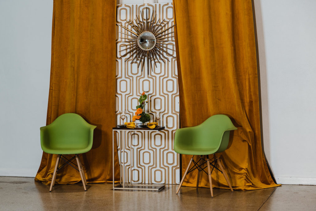 Retro Mid Century Modern Wedding Decor, Yellow Mustard Drapes, Gold Geometric Wall Panel with Starburst Mirror, Green Eames Chairs, and Vibrant Floral Arrangement | Wedding Venue Tampa Garden Club