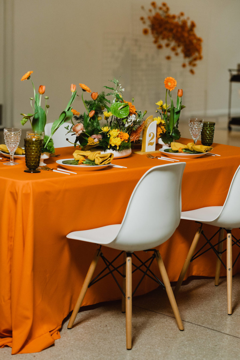 Retro Eclectic Wedding Reception Decor, Long Table with Orange Tablecloth, White Eames Chairs, Vibrant Floral Centerpieces | Wedding Venue Tampa Garden Club