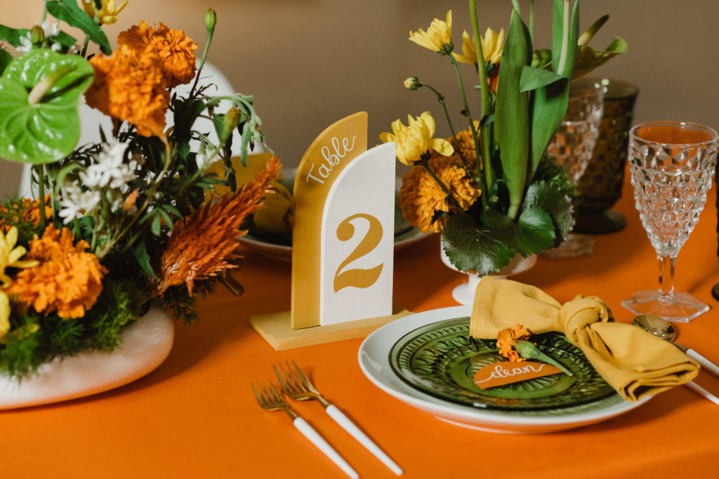 Retro Eclectic Wedding Reception Decor, Long Table with Orange Tablecloth, White Dinner Plate and Vintage Green Plate, Mustard Yellow Napkin, Geometric Yellow Table Number, Vibrant Floral Centerpieces, Yellow Flowers, Orange Marigolds, Green Anthuriums