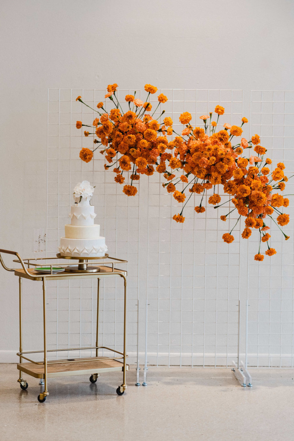 Vintage Bar Cart with White Four Tier Wedding Cake, White Cage Panel with Orange Marigolds