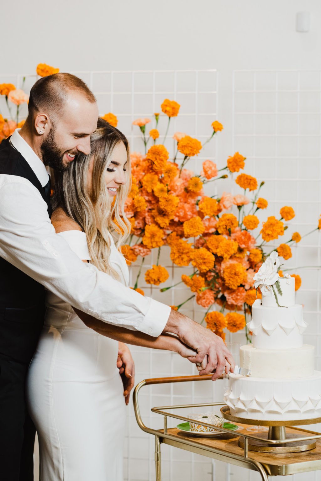 Retro Bride and Groom Cutting Four Tier White Wedding Cake on Bar Cart, Orange Marigolds