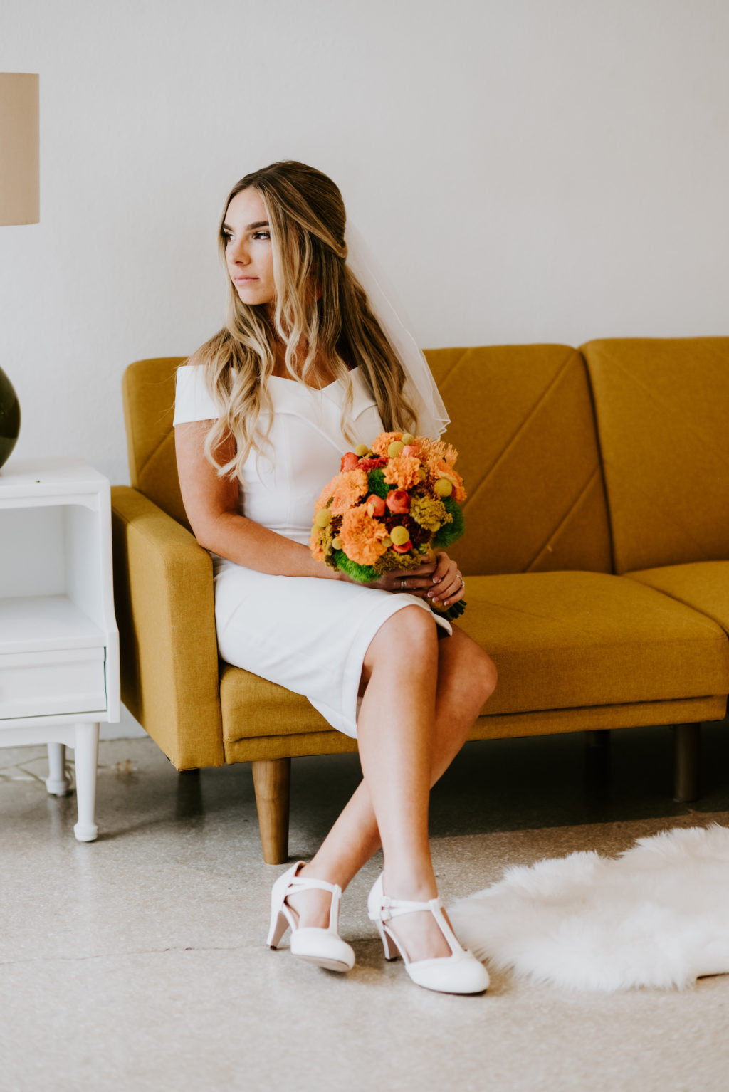 Retro Mid Century Modern Bride in Mid Length Off the Shoulder Classic Wedding Dress, White Mary Jane Wedding Shoes, Holding Colorful Orange, Marigold, Yellow, Greenery Floral Bouquet