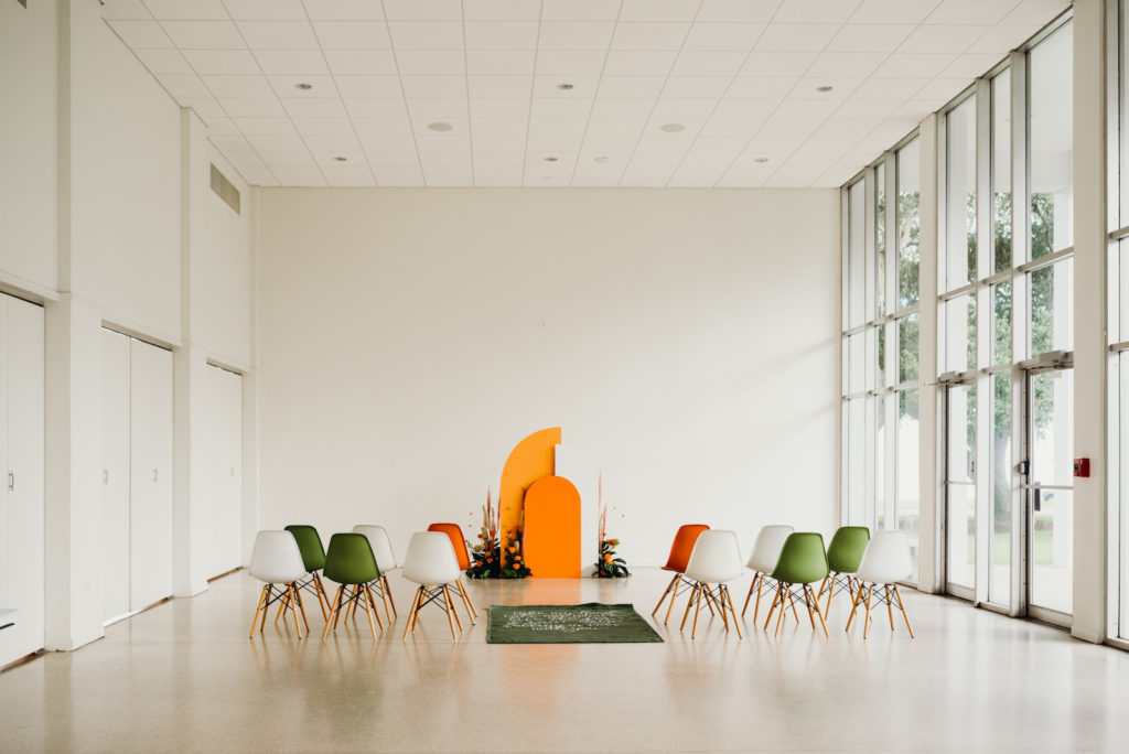 Retro Mid Century Modern Wedding Ceremony Decor, Orange and White Geometric Rounded White and Orange Arch, Green, White and Orange Chairs, Green Aisle Runner | Wedding Venue Tampa Garden Club