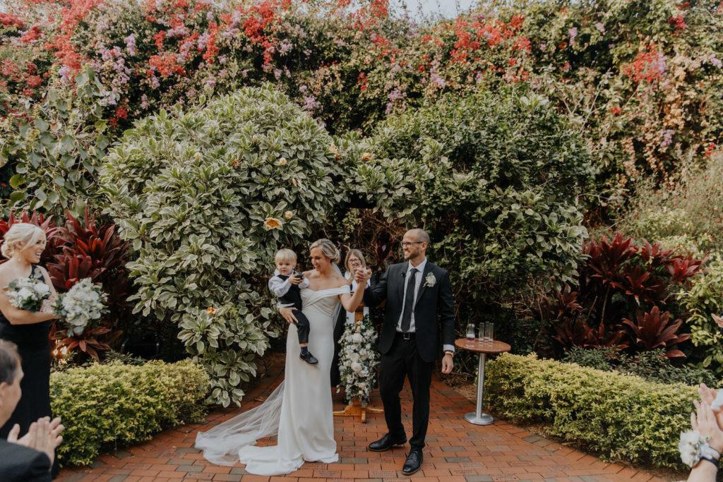 Bride and Groom Holding Child After Wedding Ceremony Portrait   St. Pete Outdoor Garden Wedding