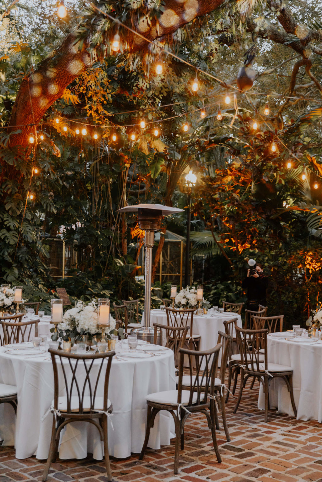 St. Pete Outdoor Wedding Reception Under the Palms with Cafe Lighting   Sunken Gardens   Crossback Wooden Chairs and Natural Centerpiece Decor