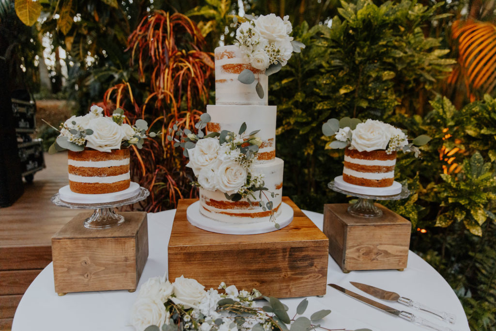 Natural Wedding Cake Display with Naked Cakes with White Roses and Greenery Decor on Stained Wooden Cake Stands
