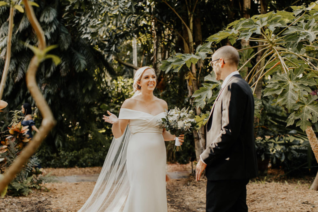 Classic Florida Bride and Groom First Look at Sunken Gardens in Downtown St. Petersburg, Bride Wearing White Fitted Off The Shoulder BHLDN Wedding Dress, Groom in Classic Black Suit and Tie   Tampa Bay Hair and Makeup Artist Femme Akoi Beauty Studios