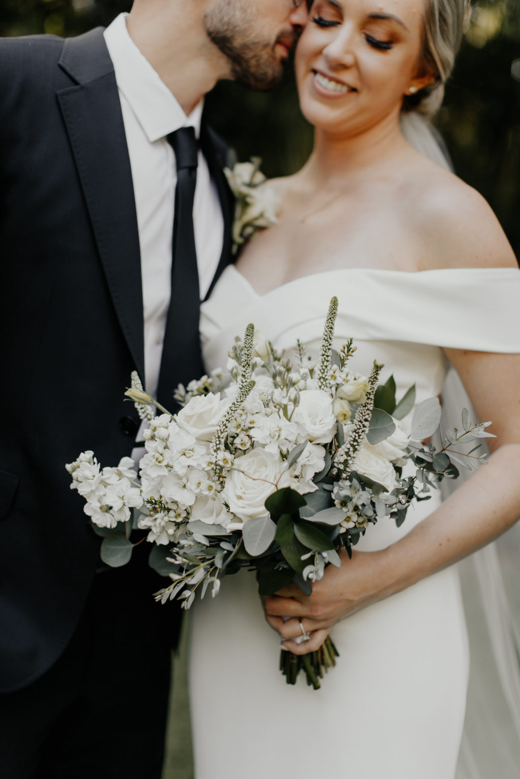 Classic Florida Bride and Groom, Bride Holding Delicate White Floral Bouquet with Greenery, Wearing Fitted Off The Shoulder BHLDN Wedding Dress, Groom in Classic Black Suit and Tie   Tampa Bay Hair and Makeup Artist Femme Akoi Beauty Studios