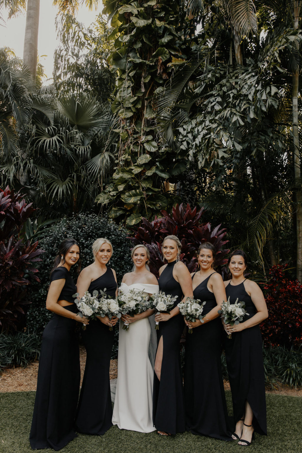 Classic Florida Bridal Party at Sunken Gardens in Downtown St. Petersburg, Brides Wearing Mix, and Match Long Black BHLDN Bridesmaid Dresses, Holding Minimalist White Floral Bouquets with Greenery   Tampa Bay Wedding Hair and Makeup Artist Femme Akoi Beauty Studios
