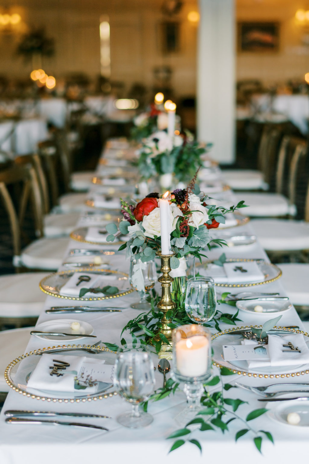 Romantic Rustic Wedding Reception Decor, Long Feasting Table with White Linens, Gold Beaded and Clear Chargers, Gold Candlesticks, Low Red and White Ivory Floral Centerpiece, Greenery Leaves Garland   Tampa Bay Wedding Rentals A Chair Affair